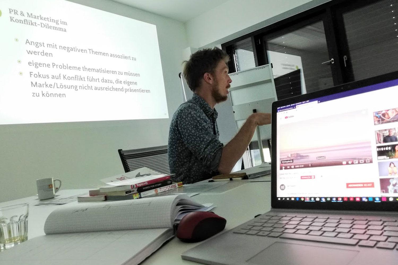 Mann bei Vortrag vor Bildschirm
